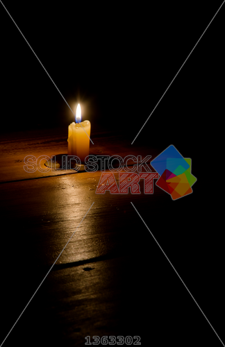 stock photo of burning candle on a dark wood background