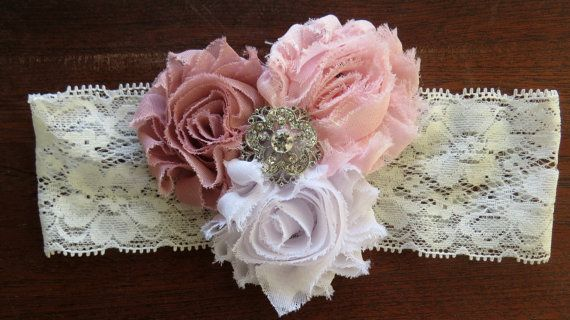 This vintage inspired baby headband features three 2.5 shabby roses in white, light pink, and mauve. It is adorned with a luxurious