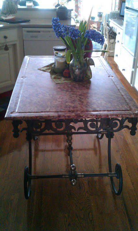 Here An Antique French Pastry Table Is Used For A Center Island. Heavy Iron  Scrolled