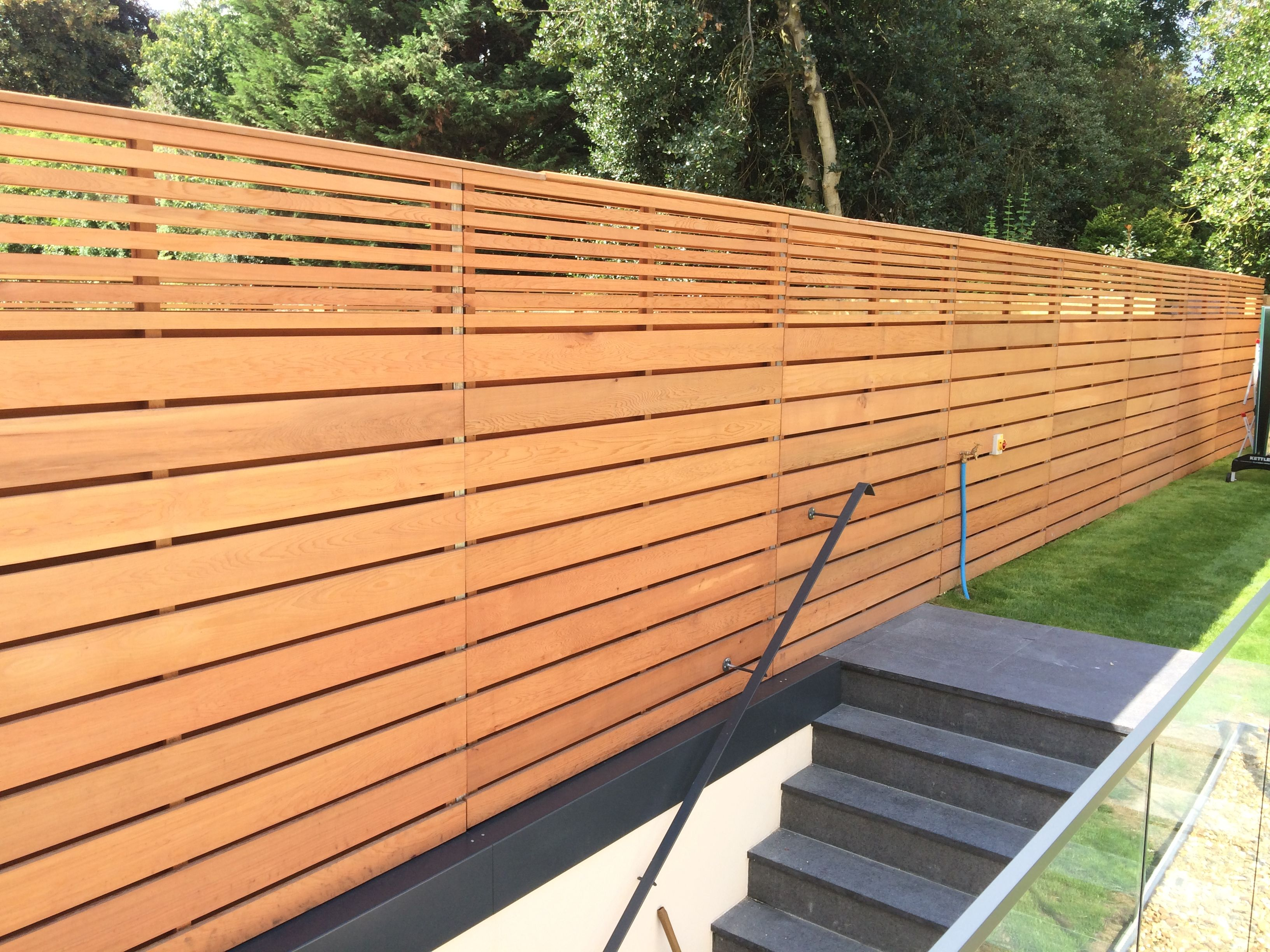 Cedar slatted fencing with a combination of large and