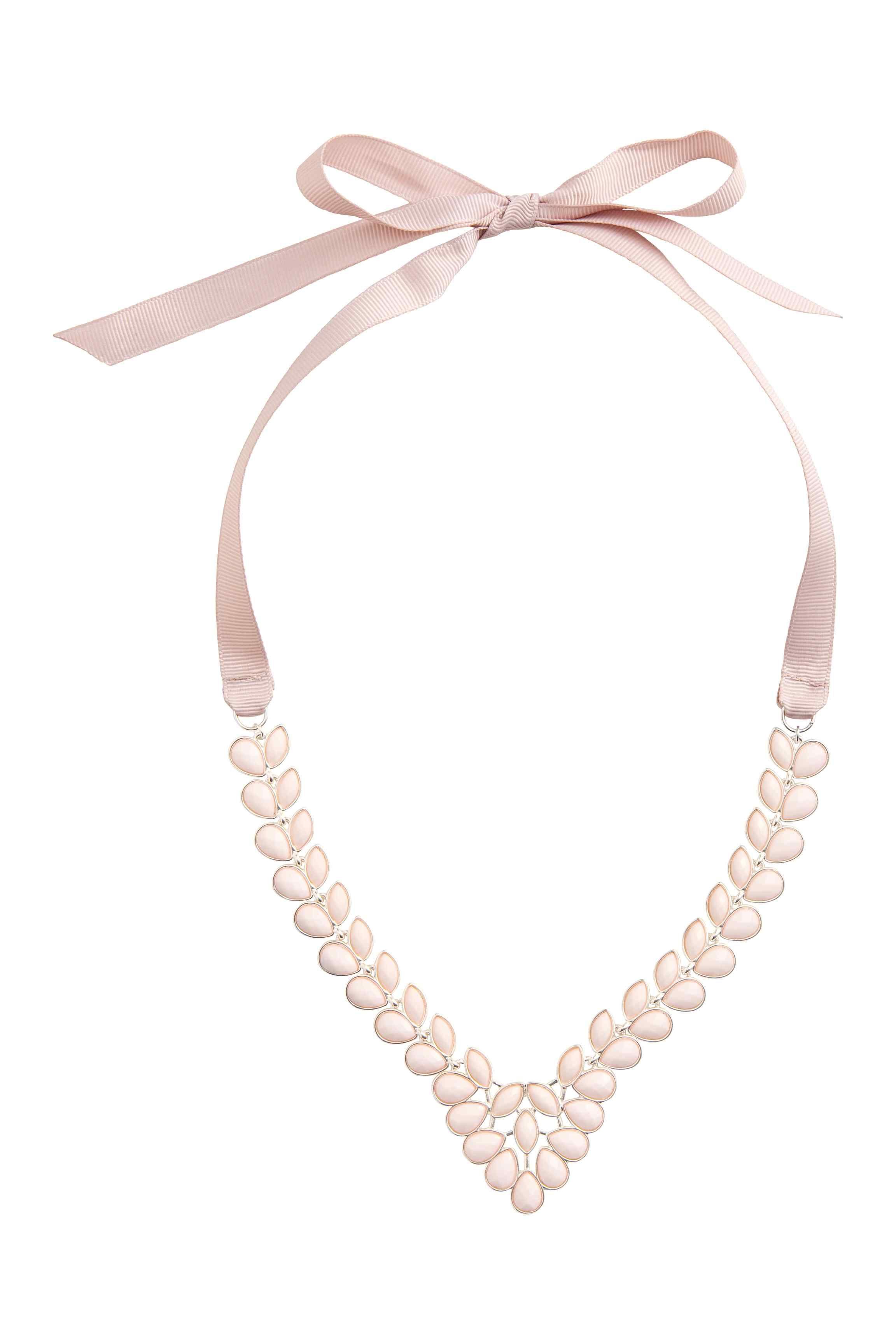 Náhrdelník se stuhou: Kovový náhrdelník s fazetovanými plastovými korálky. Má nastavitelnou délku díky grogrénové stuze, která se zavazuje za krkem.