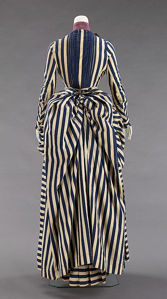 Haute Couture Victorian fashion dress gown American 1885-1888. #Historical #Costume made from cotton and silk. Printed stripe textiles were fashionable in sporting activities throughout the 19th century due to the nautical theme and their jaunty air which inspires vigor. Although the silhouette remained the same, high neckline, long sleeve with the skirt style pleated at the front and a natural flow bustle train at the back. The trimmings were reduced. #Hautecouture #Vintage #Victorian…