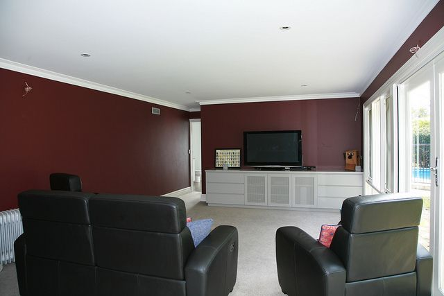 Maroon painted walls with grey carpet and grey cabinetry