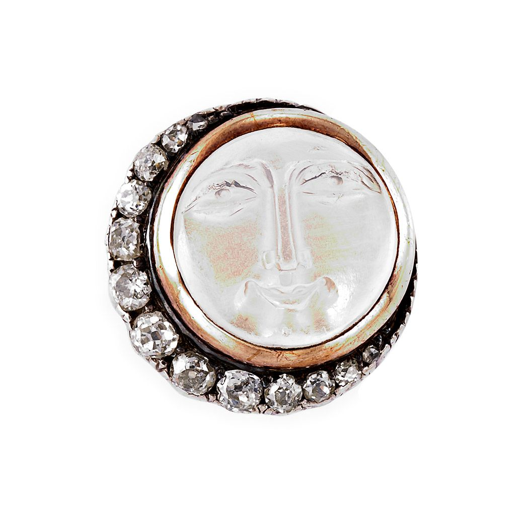 """A victorian brooch, with a carved rock crystal """"man in the moon"""" face, with a diamond crescent, set in silver and gold."""