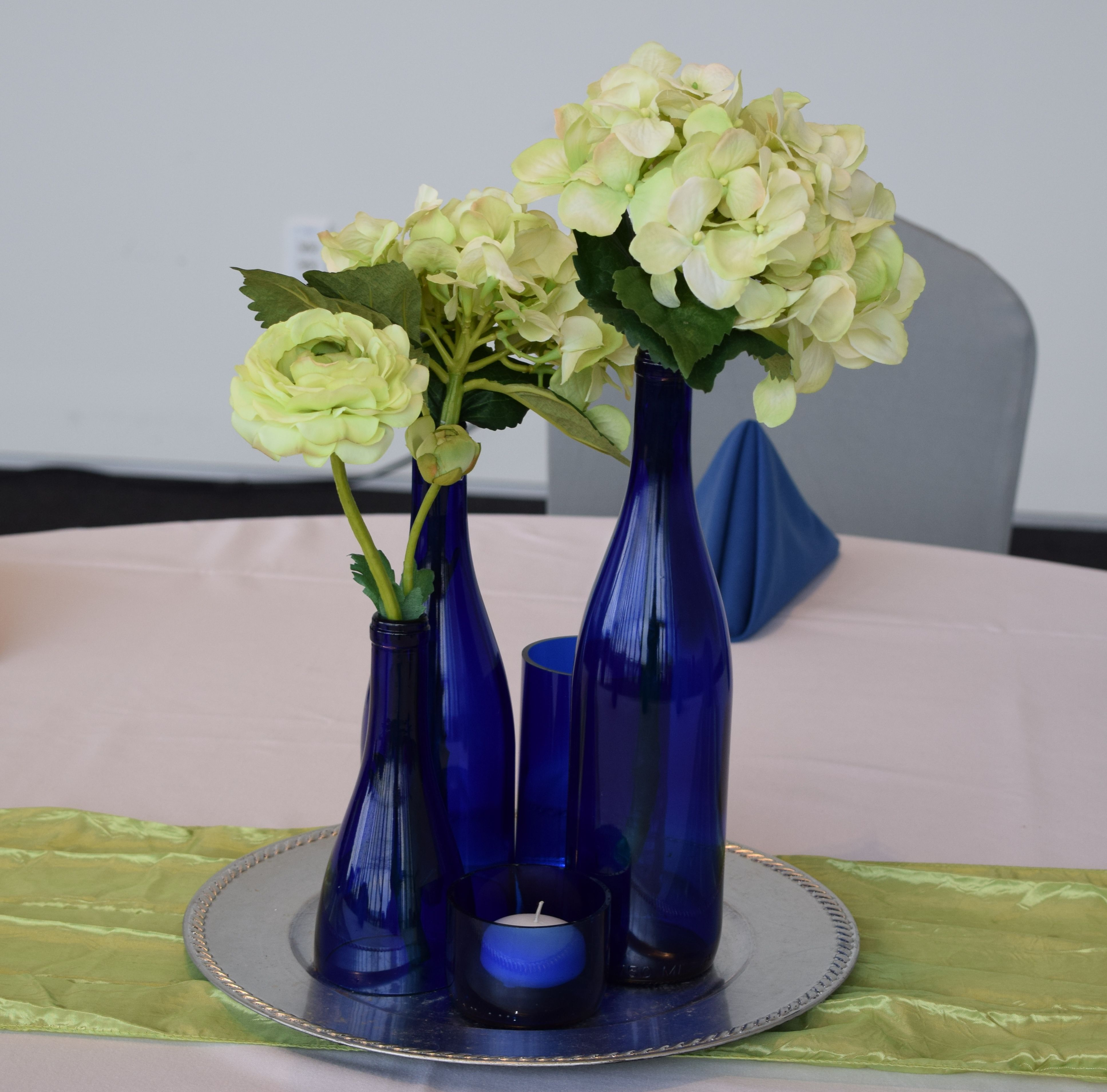 Blue glass vases green flowers and candle centerpiece