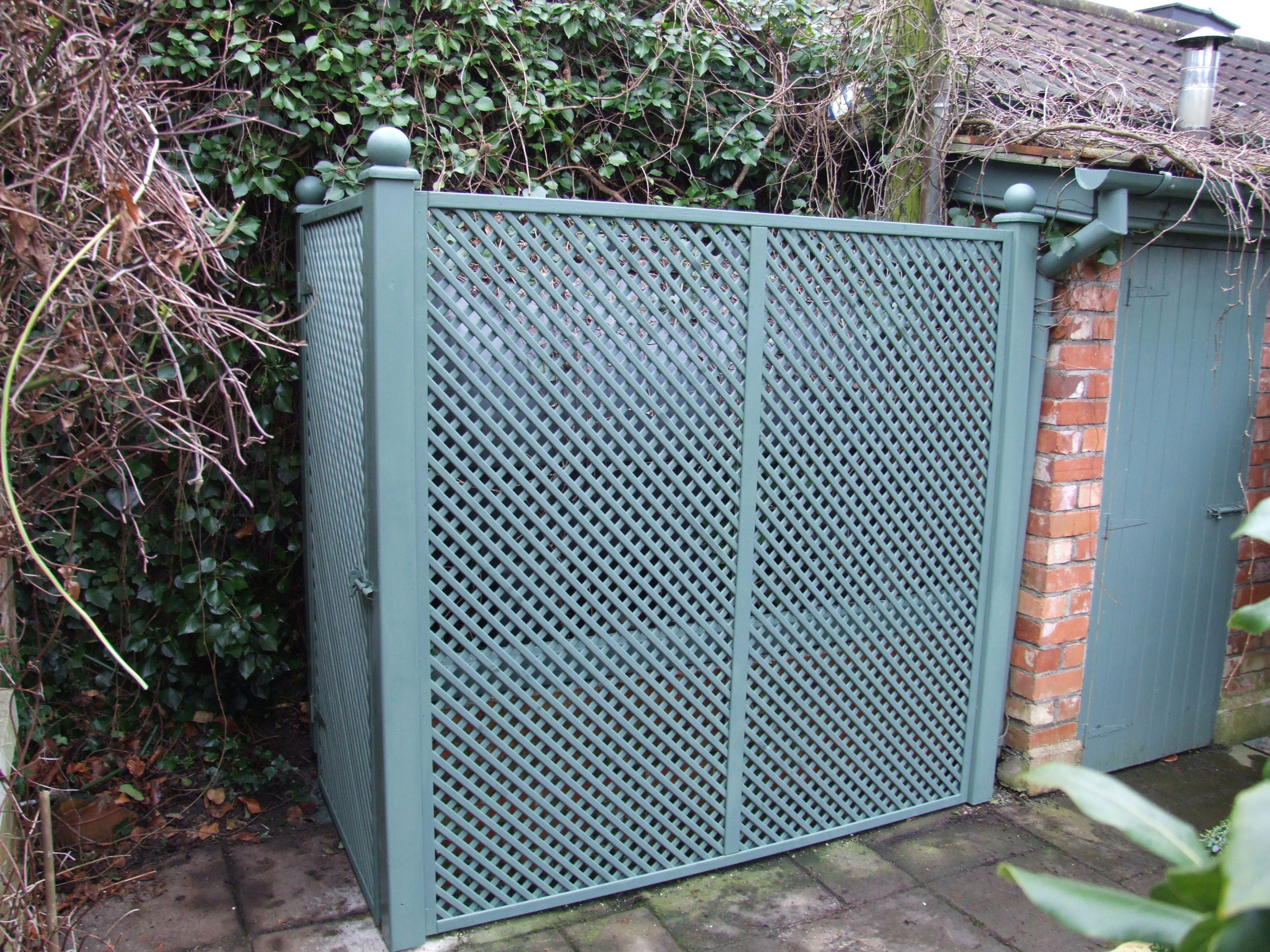 a clever use of timber trellis to hide an oil storage tank painted beautifully to