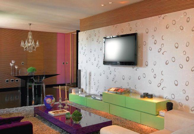 Neste ambiente, as cores aparecem em tons fortes nos móveis, como a estante sob a TV e a mesinha de centro, que tem acabamento com brilho. Outro ponto que chama a atenção é o papel estampado que reveste uma das paredes  Arquivo / Casa e Jardim