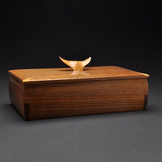 """This Walnut jewelry box has a hand carved whale tale (maple) for a handle. It has a removable tray for small pieces of jewelry. The box is line with felt (burgundy). The walnut is finished with an amber shellac which gives a warmth to a wood that sometimes can look cold if finished with a clear finish.  Dimensions 13""""L x 7 1/2W x 4""""H"""
