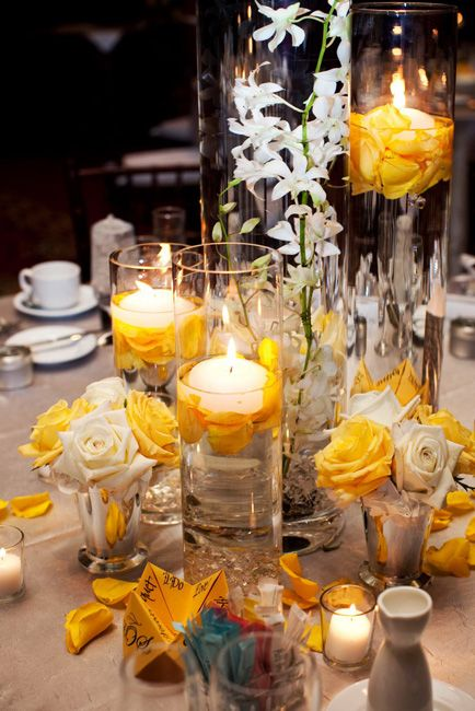 Rose petals line floating candles in glass pillar vases