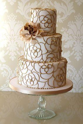 Tarta nupcial en blanco y dorado con detalle de flor natural teñida al tono