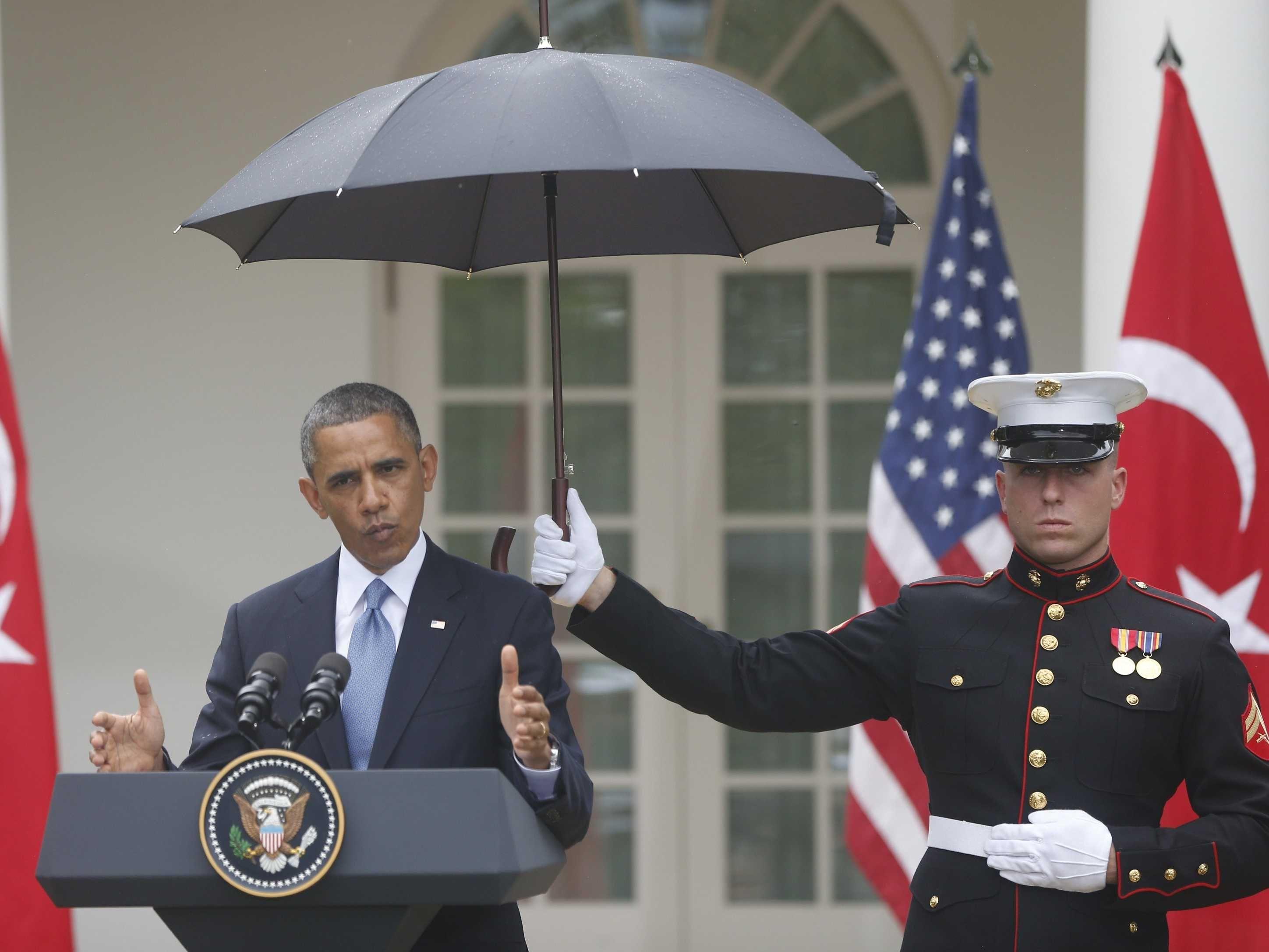 Marine Holding Umbrella For Barack Obama