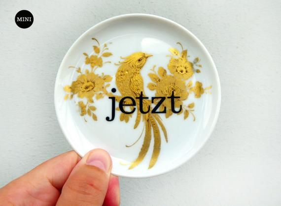Herr Fuchs makes into dishes.Our Vintage wall plate with our jetzt typo is a special piece for your wall.Every plate is hand manufactured and each of the vintage plates is a single item again and again. This variant has a gold bird and  and with our jetzt he can become Deko on the wall or in your bookself .Every plate is provided with a plate hanger. So he can to the wall at once if he reaches you.The plate has a diameter of 11cm.jetzt! Sometimes it is difficult to be in the moment and to percei