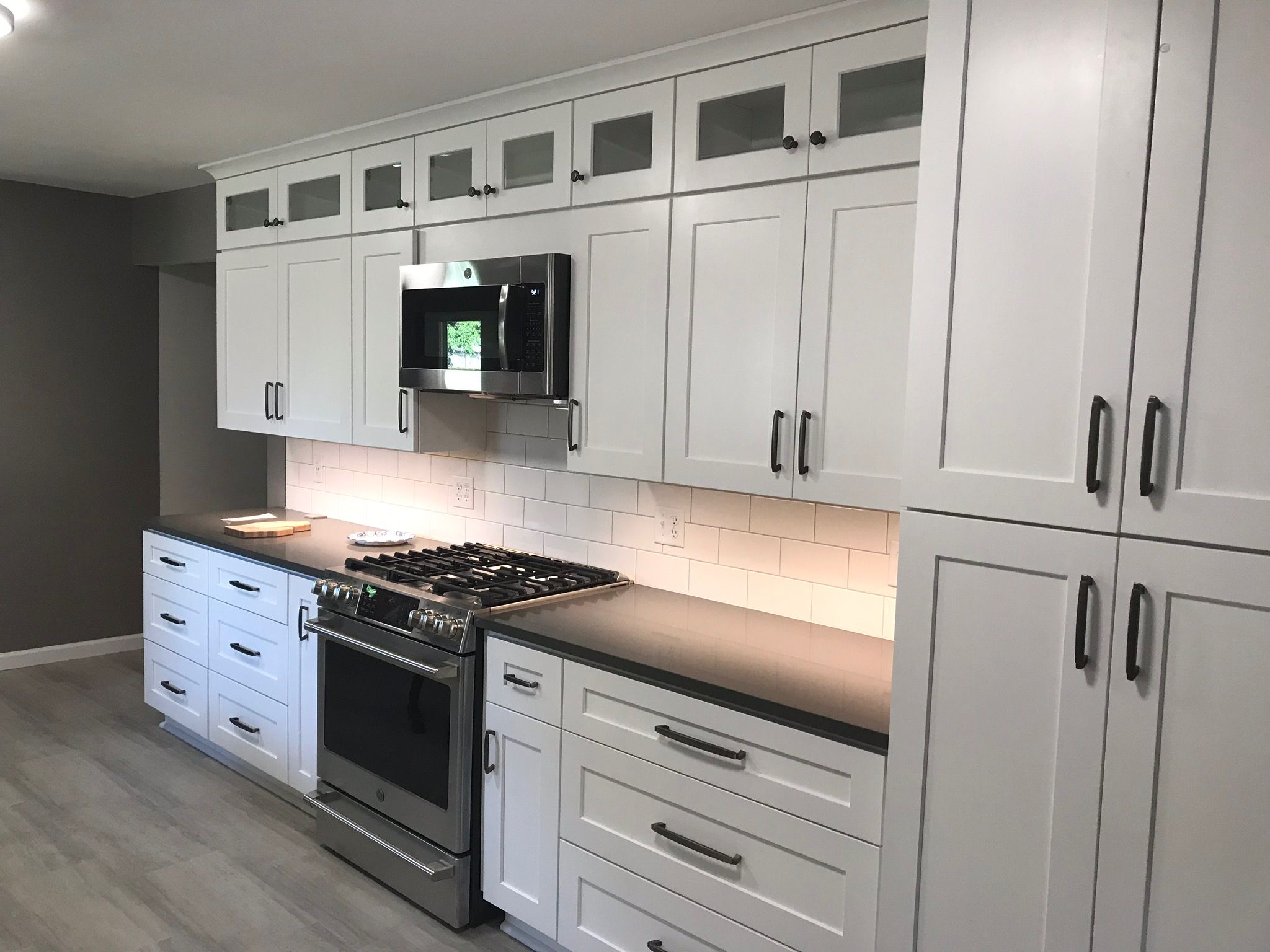 Photo of Vakre J & K-hvite rysterskap installert av The Wood Door. Kvarts teller …