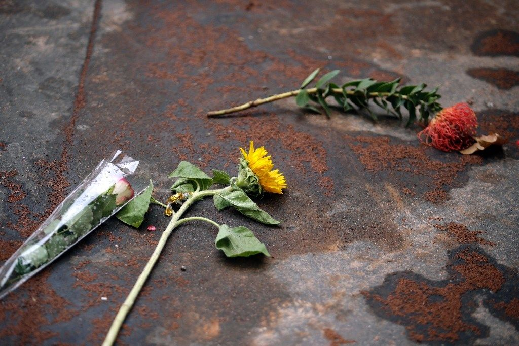 Flowers lie in the sand left to absorb bloodstains near a cafe targeted in the November 13 jihadist attacks in ParisFlowers lie in the sand left ...