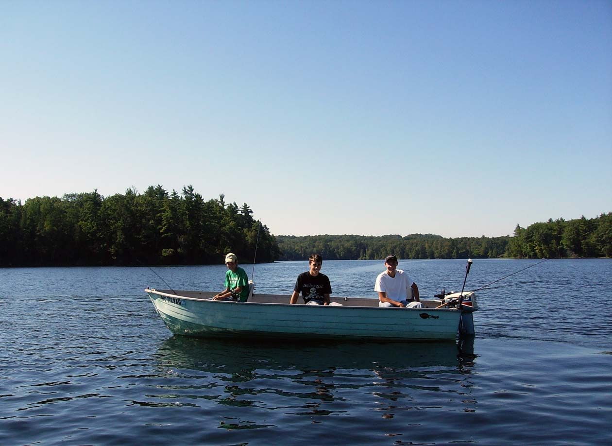 Three men in a boat, fishing on a lake.