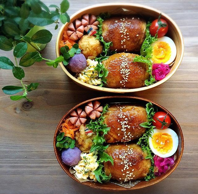 Chicken-wrapped onigiri bento box, featuring hard boiled egg, pickled cabbage, and ...