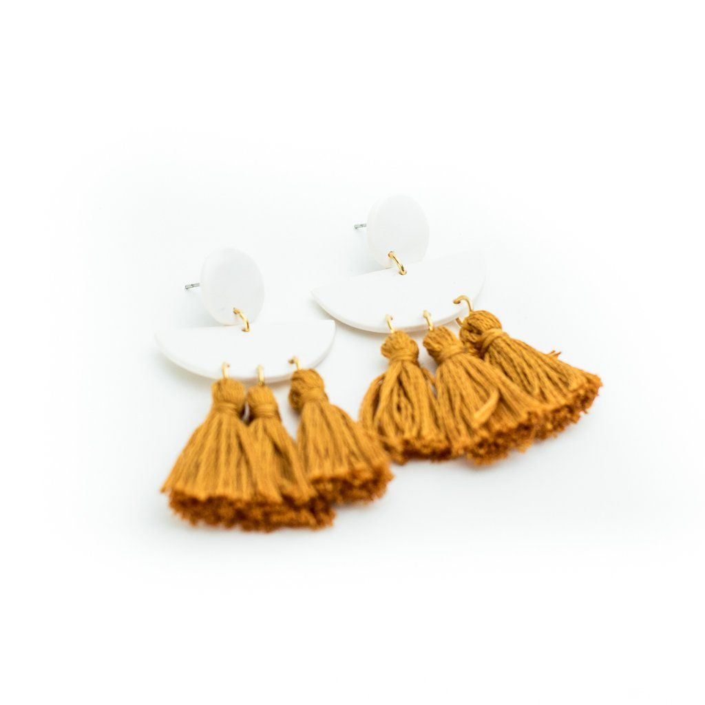 These fringe clay earrings feature white clay shapes and a three blush hanging tassel for a fun look. Made by a local artisan in Holmes County. SIZING: 2