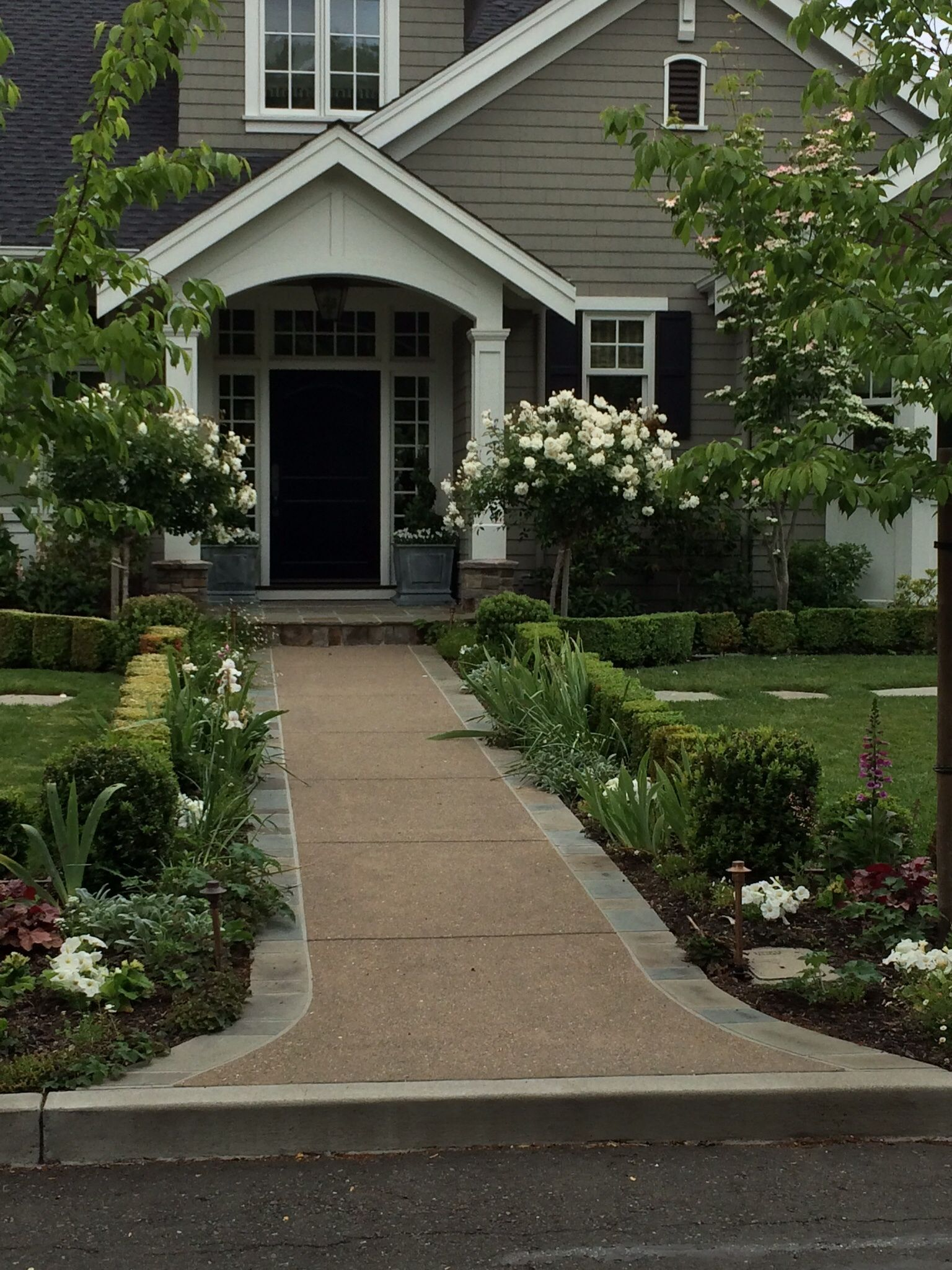 Layering with boxwoods could do this along sidewalk to for Front door garden ideas