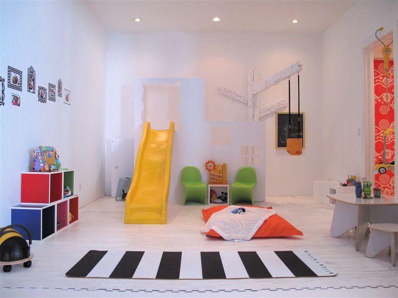 salle de jeu pour enfants avec toboggan jaune et tapis noir et blanc rayé