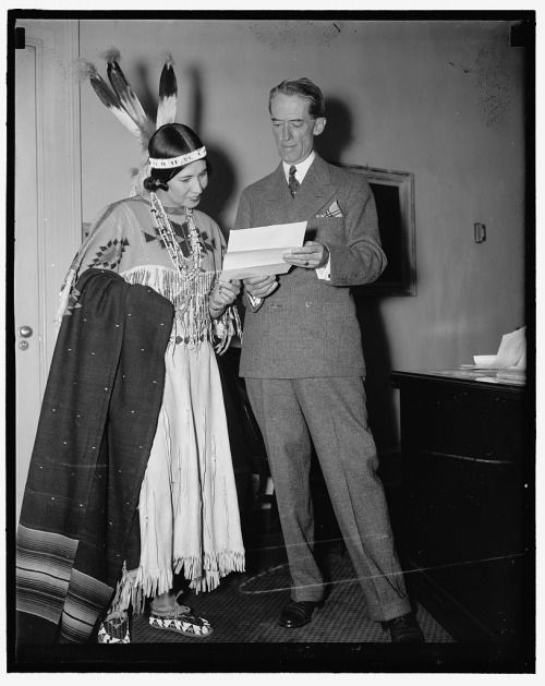 Original caption: Dressed in full regalia, Princess White Deer, extended an invitation to President Roosevelt at the White House today to attend the Six Nations Iroquois Grand Indian Council July 5 at St. Regis Reservation. The Princess; who is shown with Presidential Secretary Marvin H. McIntyre said the Indian powwow will be the first time Iroquois Indians have held their council since pre-revolutionary days. 6/28/37   Princess White Deer was the stage name of Mohawk performer Esther…