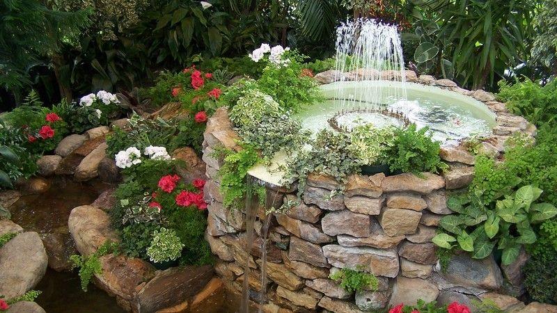 Springbrunnen aus Stein mit Wasserspiel im Garten, umgeben von Pflanzen Gartenteich