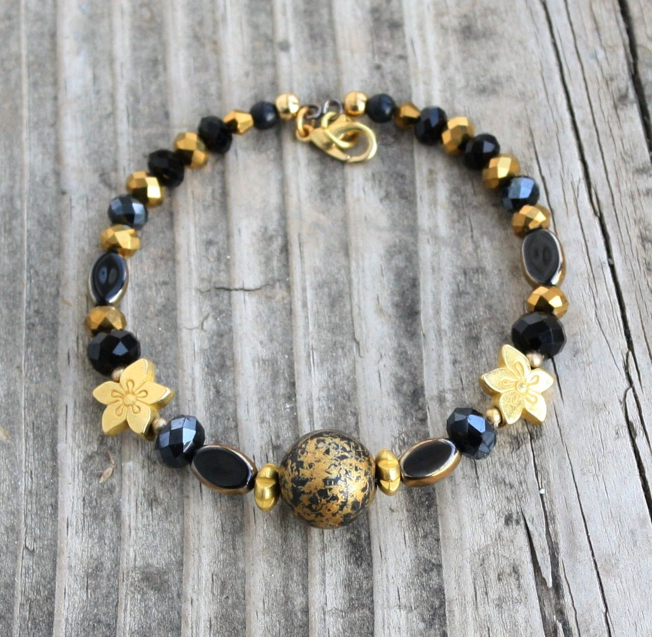 Black & Gold Pewter Flowers Memory Wire Bracelet $12.00  This rich bracelet is made with oval gold over black glass beads, faceted black and gold crystals, a black and gold acrylic focal bead and pewter spacers and flowers on memory wire with a gold plated lobster clasp.  This can be adjusted to any size upon request.
