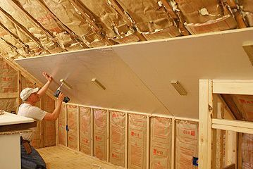 Rigid Foam Insulation Being Hung From Sloping Ceiling