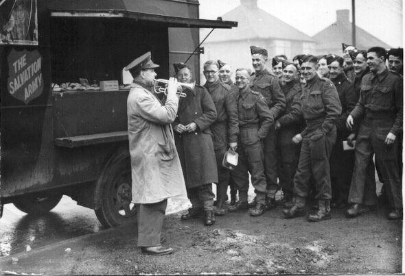 Kanadische Soldaten stehen während des Zweiten Weltkrieges vor einer mobilen Kantine der Heilsarmee Schlange.