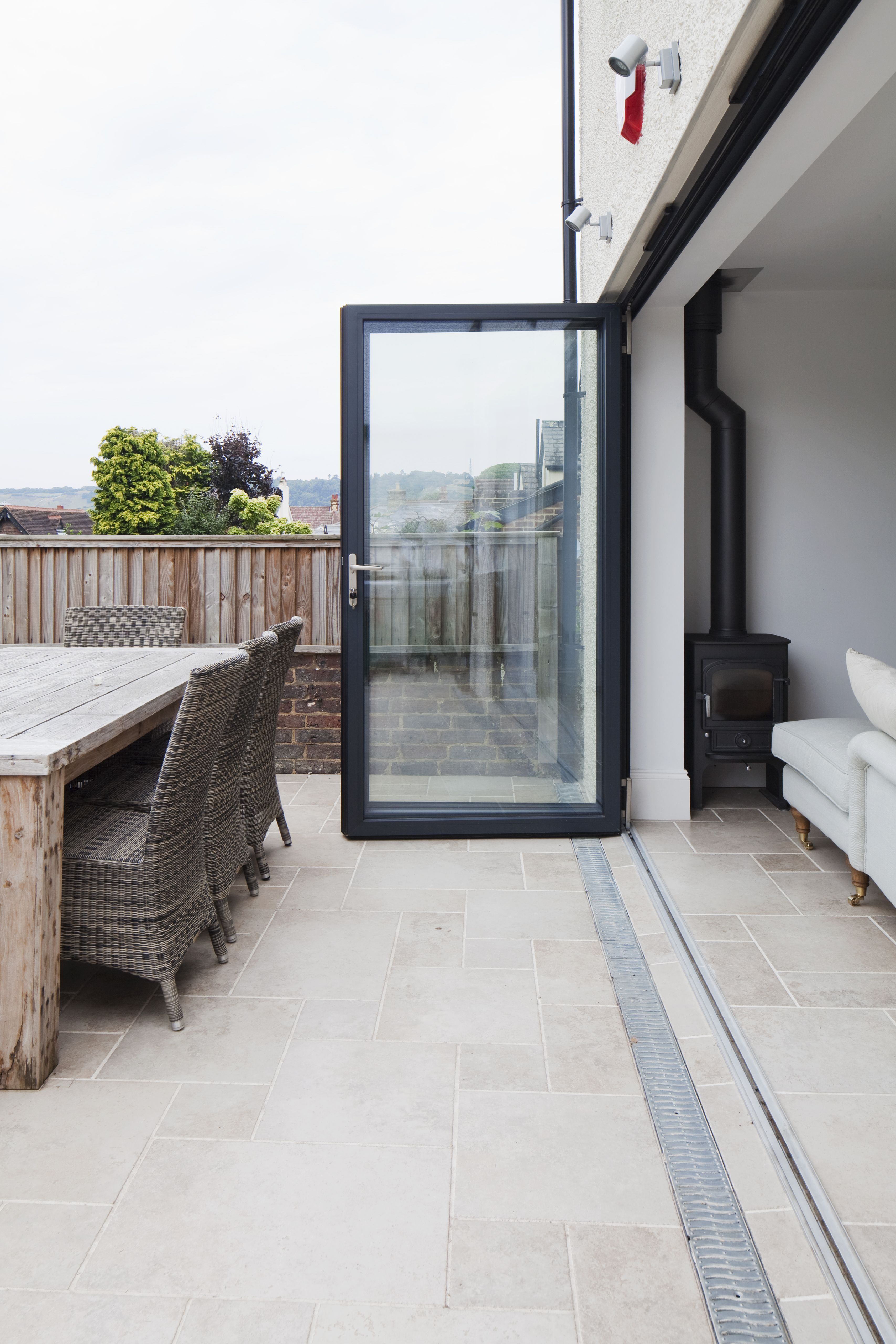 Aluminium Bi Fold Doors Level Threshold With Stone Floor Seamlessly Connecting Inside And Outside Spaces Con Patio Flooring Outside Flooring House Exterior