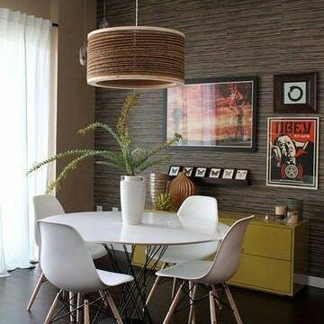 Sala de jantar com mesa dos pés em ferro e tampo branco, cadeiras Charles Eames brancas, piso laminado café, luminária pendente e quadros na parede. Buffete amarelo e parede revestida em madeira.