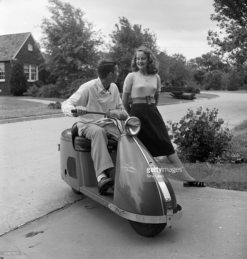 A teenage boy sitting on a motor scooter and having a conversation with a girl in Tulsa, OK in 1947.