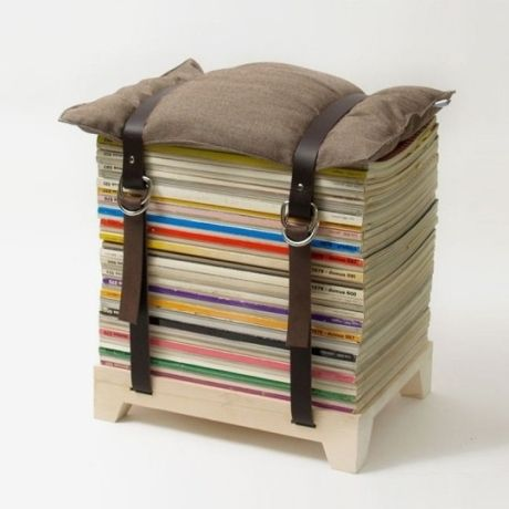 a stool made of old magazines a wooden stand and a tied down pillow