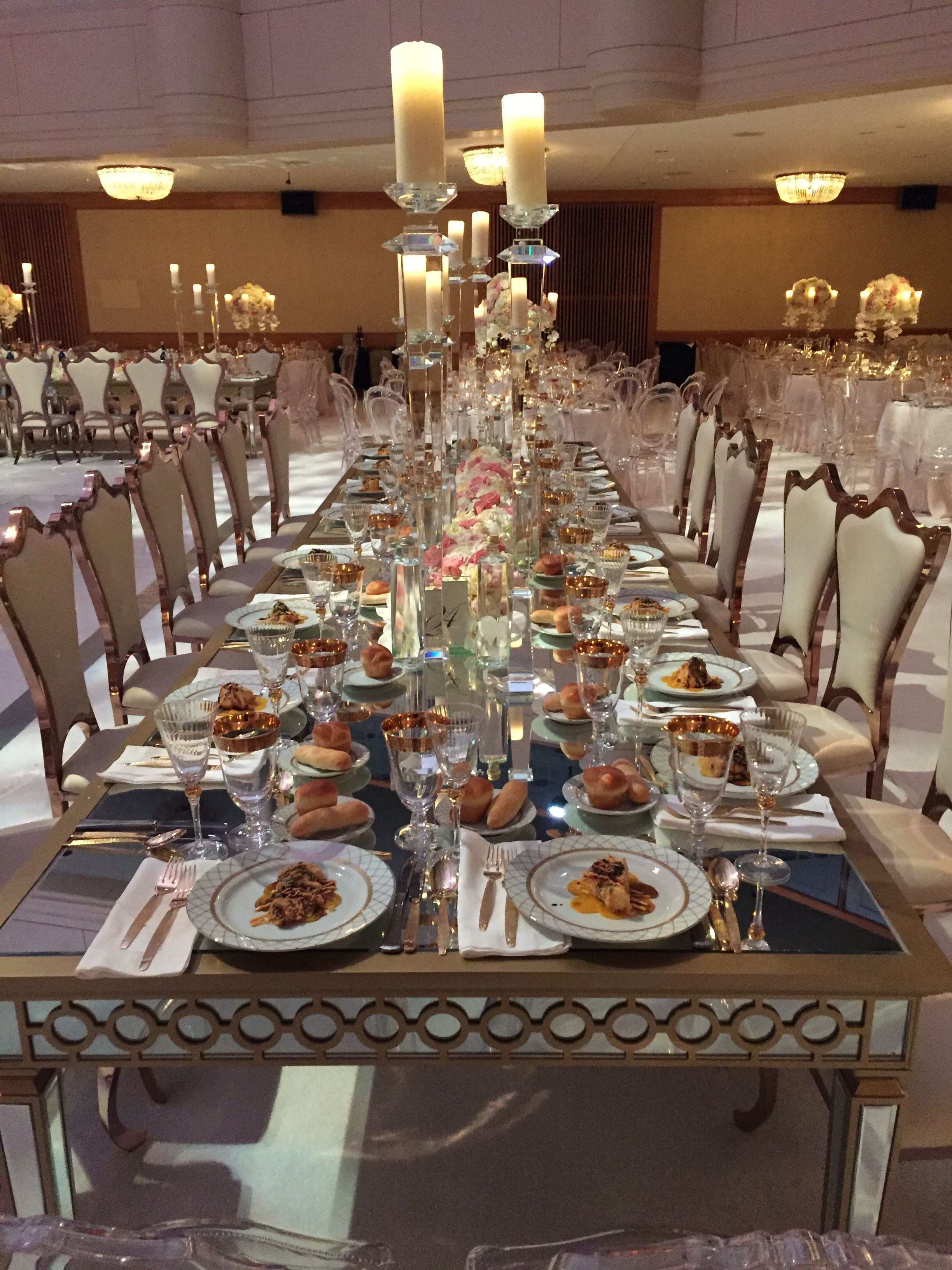 mirrored banquet table with floral garland and crystal candlesticks