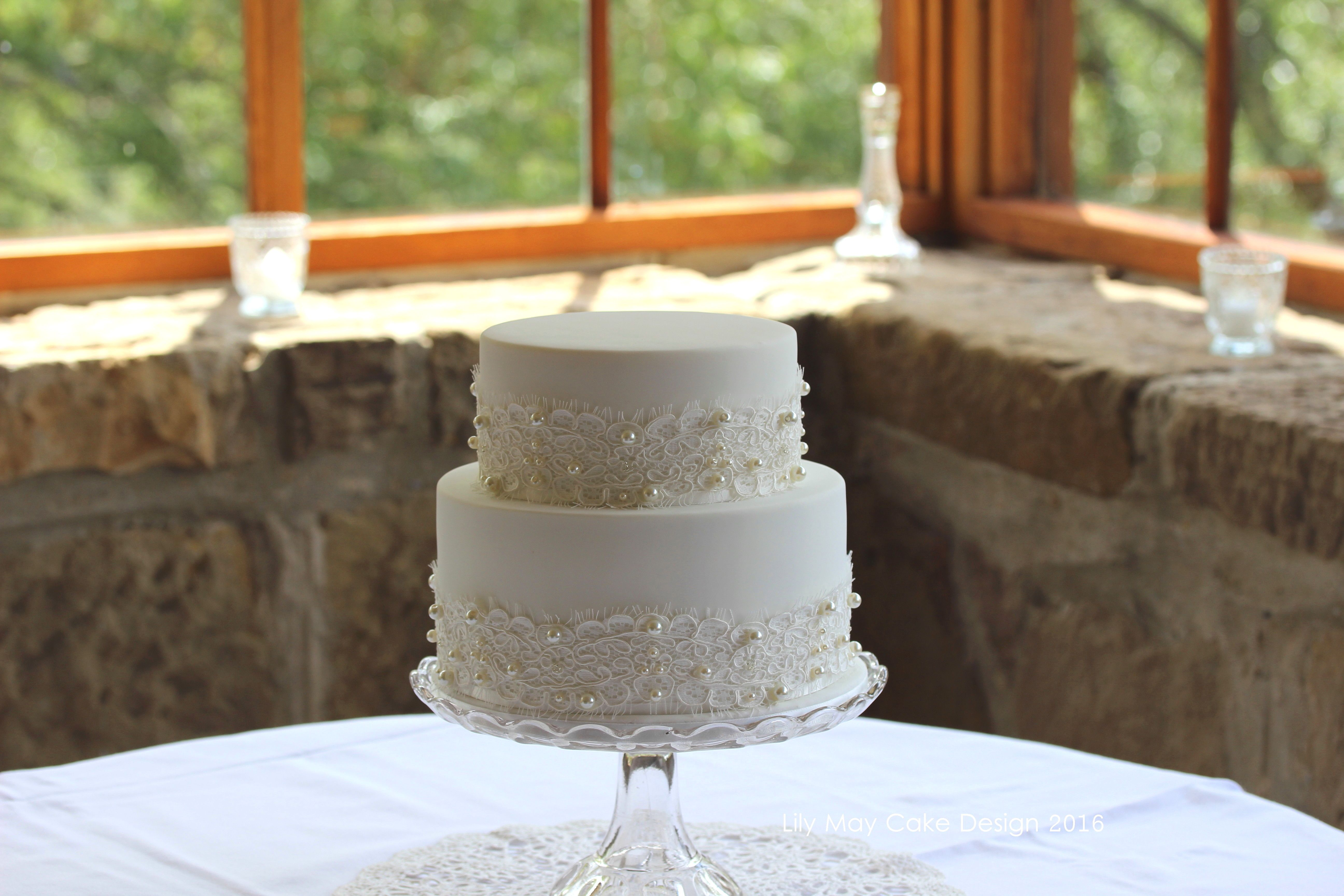 Sweet little two tier wedding cake with pearl embellished lace