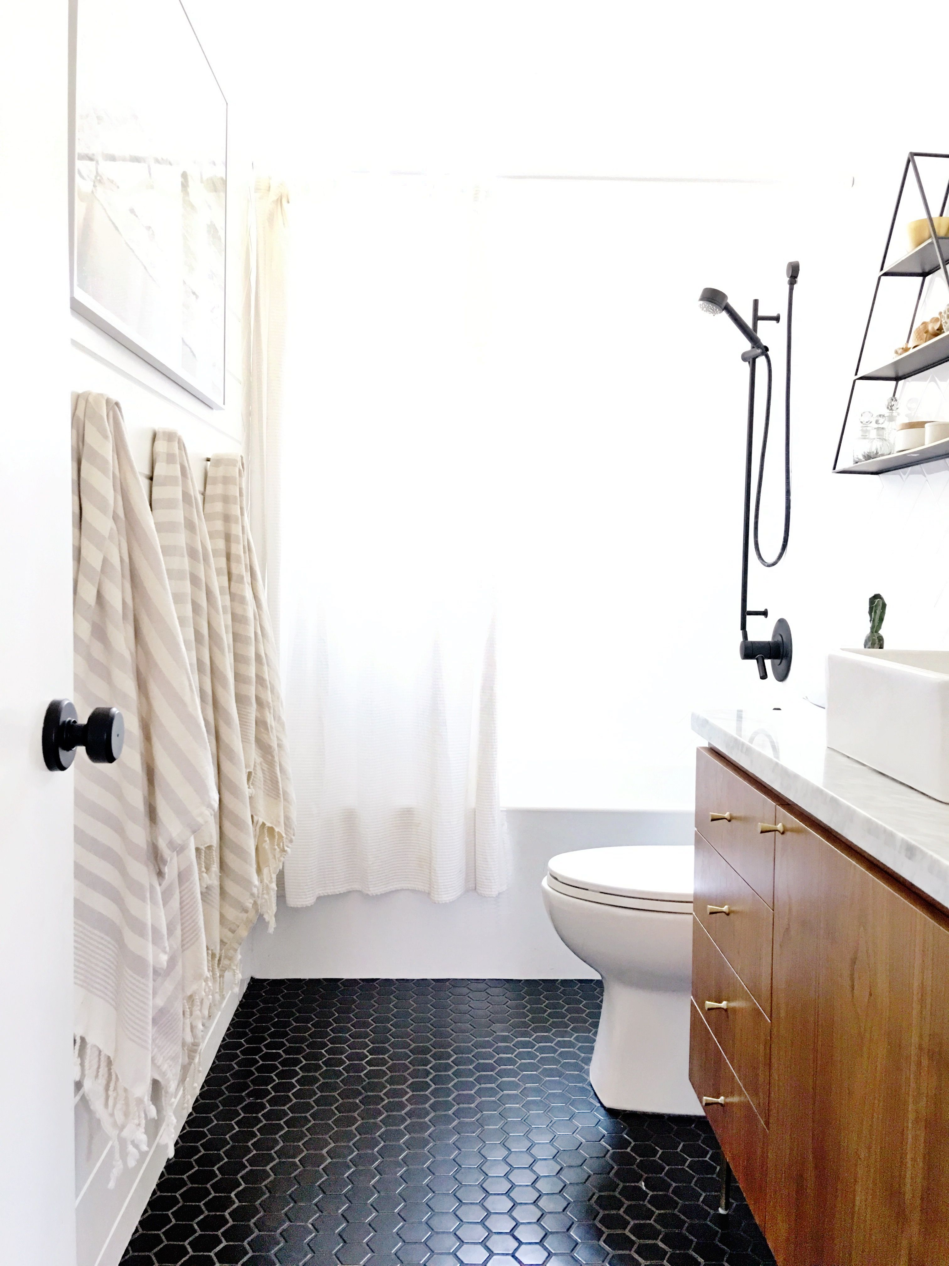 Walnut bathroom vanity with gold hardware, black floors, white walls ...