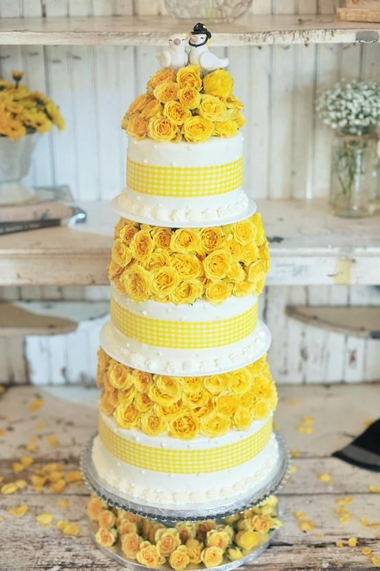 Adorable three layers wedding cake with yellow roses and a pair of ...