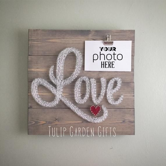 What an adorable addition to your photo wall. And makes a great wedding or shower gift! This 14 x 14 hand built pallet style wall-hanging has the word Love nailed then strung with a cute little accent heart. Standard orders will be done in white and red as pictured but if you desire a different