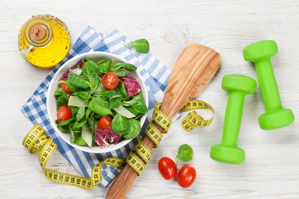 Healthy salad and fitness equipment by karandaev. Healthy salad and fitness equipment on wooden tabl...