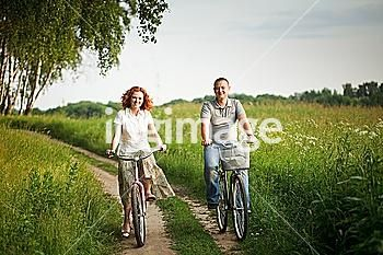Happy young couple riding on a bicycles