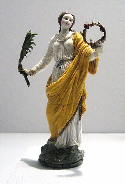 17th-century glass female saint; holding a palm branch, symbol of martyrdom, and a crown, glory.