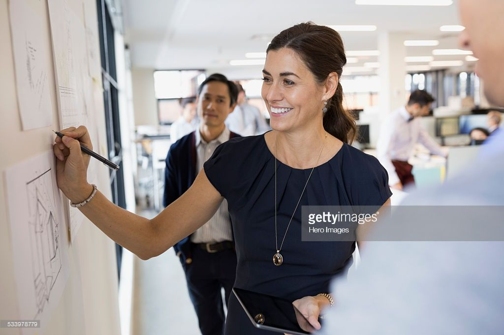 Stock Photo Smiling architect writing at wall This or