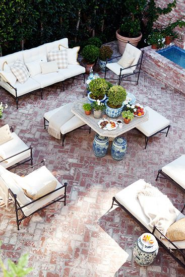 Chic patio features wrought iron sofas chairs and ottomans