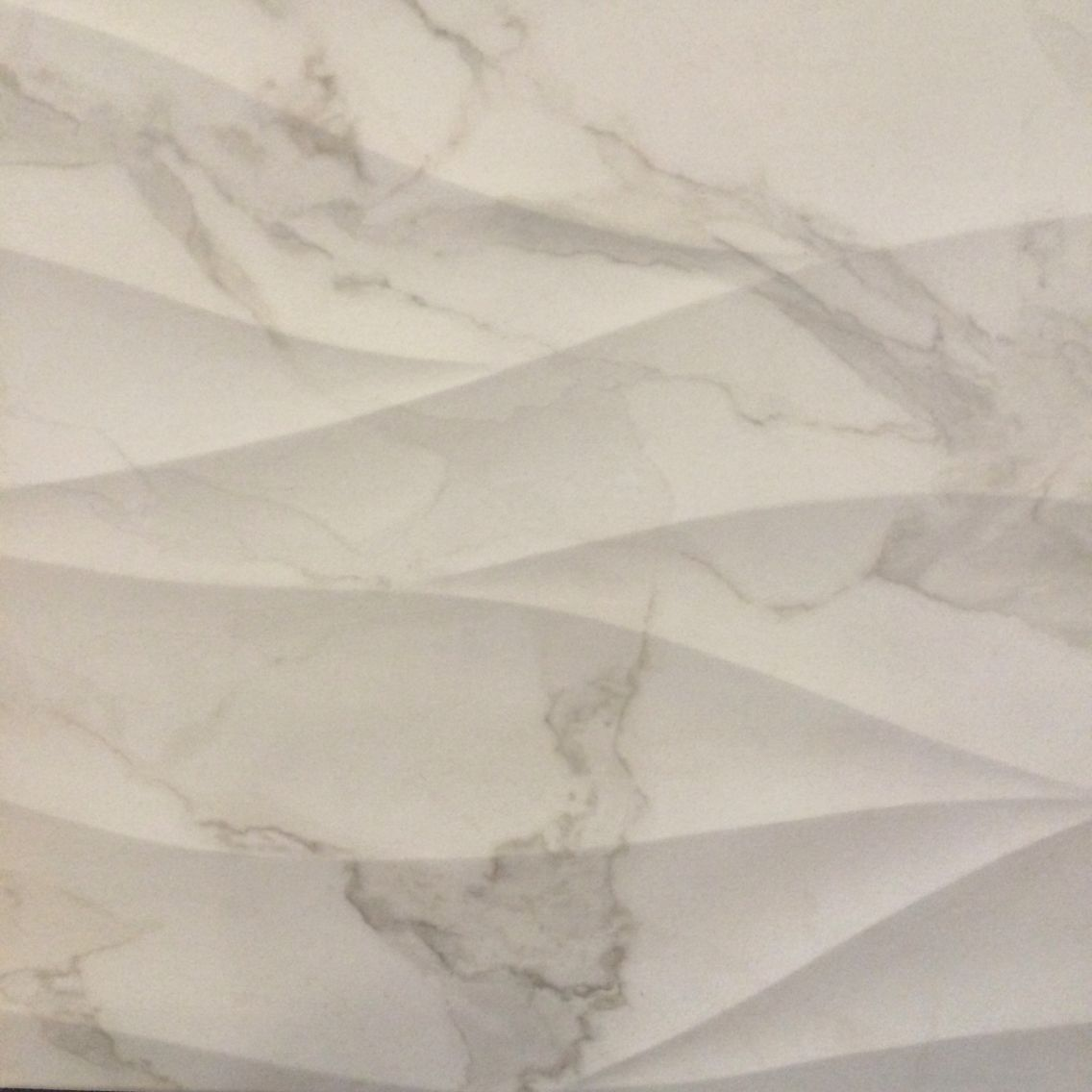 Dimensional 12x24 porcelain tiles for the walls in a Calacatta-look. We love this❤️