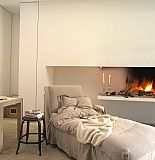 A comfy stylish chaise the raised hearth fireplacewith a