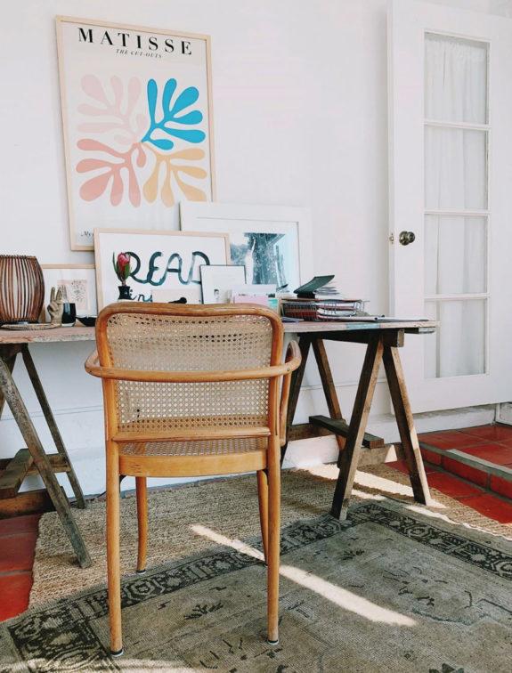 vintage sawhorse desk in home office of blogger victoria smith aka SFGirlByBay in her laguna beach cottage. #desk #homeoffice #deskchair #vintagechair #caning #sawhorse #sawhorsedesk #sawhorsetable #poster #matisse #art #artwork #framedart #vintagerugs #cottage #lagunabeach #sfgirlbybay #SFGirl