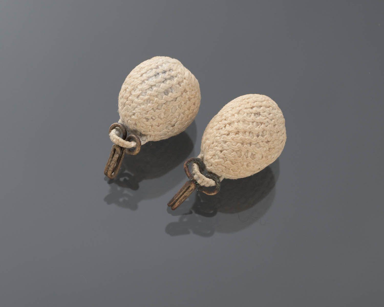 Paar eenvoudige messing akerhaakjes met eivormige akertjes van geknoopt garen. De lusjes waarmee de aker aan de haakjes vastzitten zijn gevlochten. Akertjes werden op Marken gedragen aan de punten van de schouderdoekjes. #NoordHolland #Marken