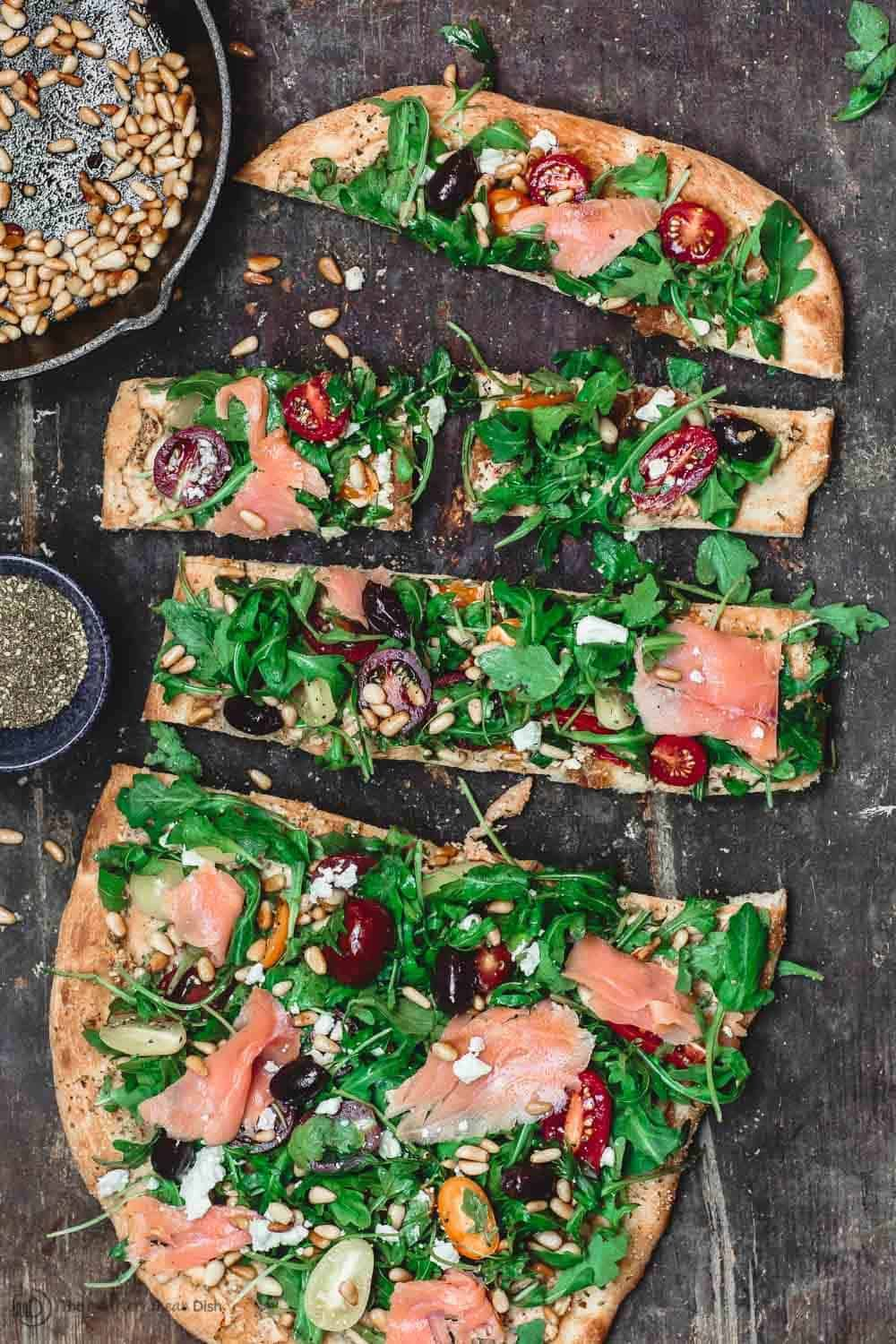 Love this Mediterranean Flatbread Recipe loaded with arugula smoked smalon and other amazing Mediterranean toppings The perfect for a crowd And good for a simple dinner w...