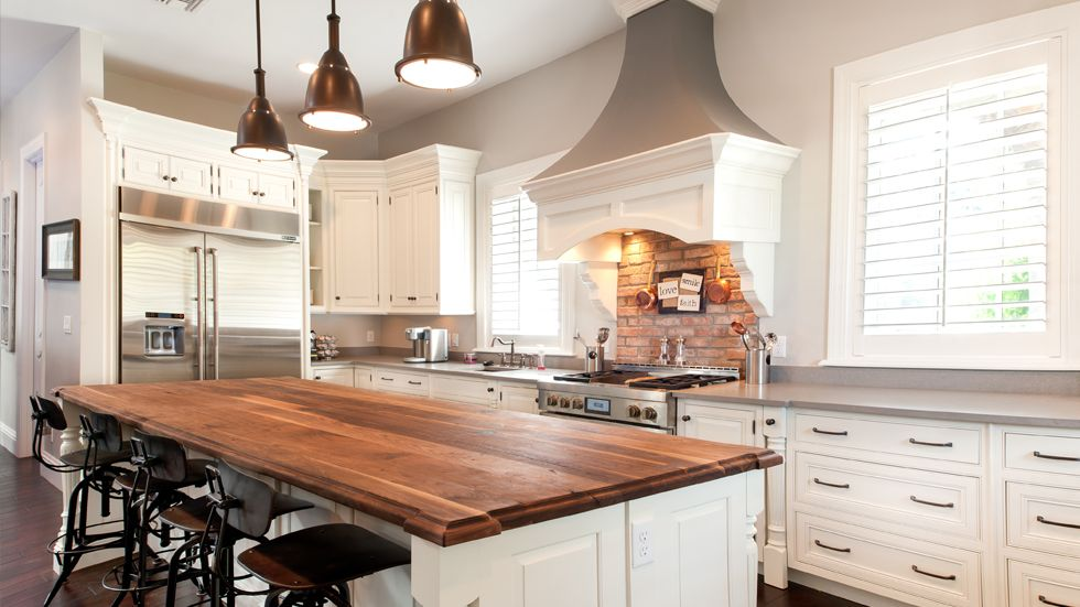 White Kitchen Exposed Brick large overhead vent hood, white molding, exposed brick wall, wood