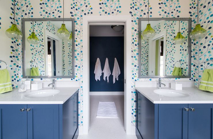 Photo of Kids' bathroom with modern tree wallpaper framing gray mirrors over blue washsta…