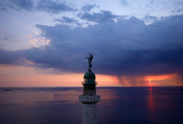 世界の美しいランドマークをドローンで空撮した写真シリーズ「Air」 > Amos Chapple(http://www.amoschapplephoto.com/) > トリエステ湾の夕日に浮かぶ世界最大級の灯台「ビットリア・ライト」(イタリア・トリエステ)